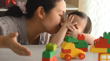 parenthood : Asian baby girl playing blocks with her mom Stock Footage