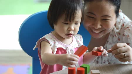 Çocuk bakımı : Little asian girl and mother playing with colorful construction blocks on table