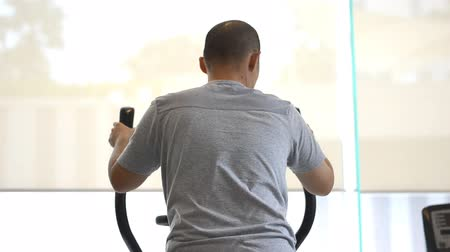 elliptical : Asian man exercising elliptical treadmill trainer in fitness gym