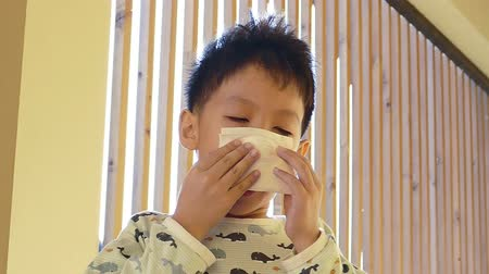 грипп : Young Asian boy wipes his nose by tissue paper ,slow motion Стоковые видеозаписи