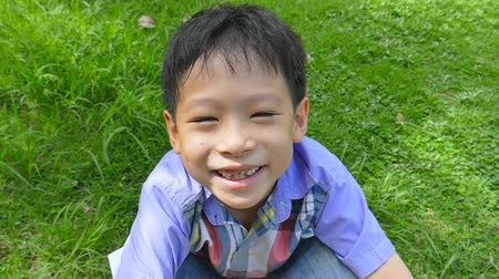výraz : Little Asian Boy Sitting In A Field Smiling And Looks At The Camera ,Slow Motion