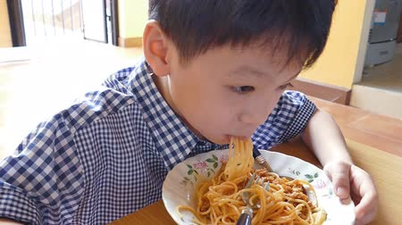 macarrão : little Asian boy eating spaghetti at home, Slow motion
