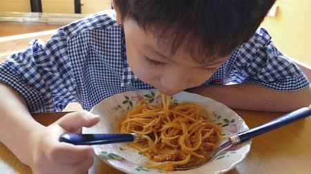 massa : little Asian boy eating spaghetti at home, Slow motion