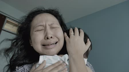 pŁacz : Asian woman is upset and crying with her little daughter