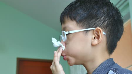 nariz : Young Asian boy wipes his snot by tissue paper