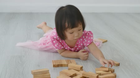 przedszkole : Little asian girl playing with wood blocks on the floor