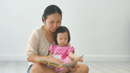 ler : Asian mother telling a story to her baby in living room