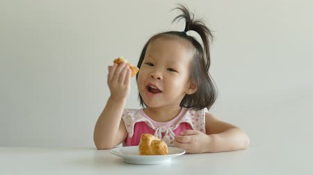 comida japonesa : Little Asian girl eating bun on the white background. Vídeos