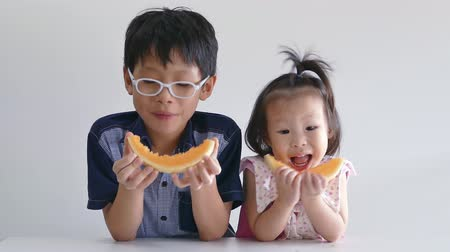 фрукты : Little asian children eating melon
