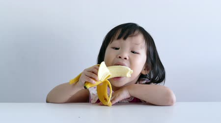 muz : Little Asian girl eating banana
