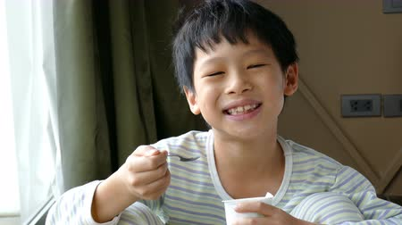 азиатский : Young Asian boy eating yogurt in at home