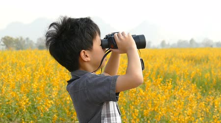 gözlem : Asian boy looking through binoculars in flower field