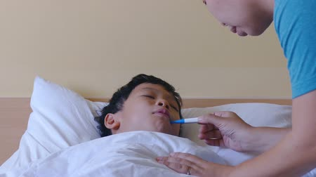 cold : Sick boy, lying in bed, mother checking his temperature