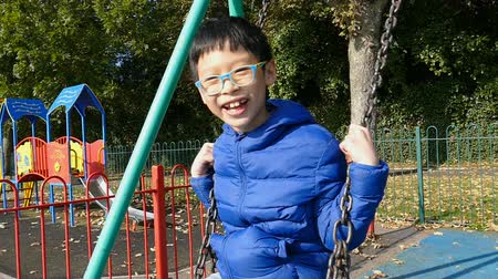 Asian smiling boy swinging in a rocking chair ,slow motion