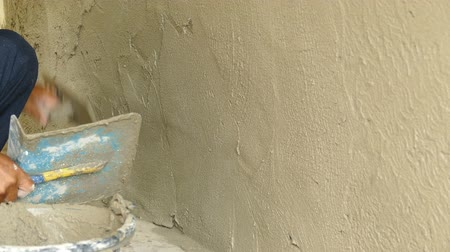 Mans hand plastering a wall with trowel