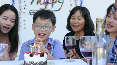içme : Asian boy blowing out candle on her birthday cake Stok Video