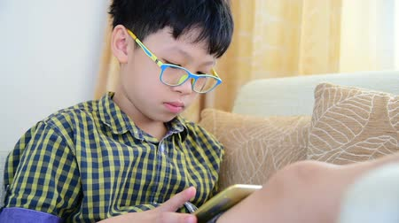Young asian boy playing games on tablet computer at home Wideo