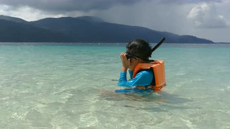 Young asian boy snorkeling with mask and snorkel in the sea water