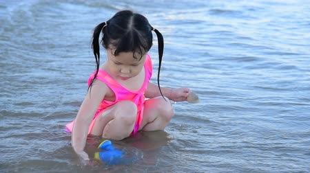 Little asian girl playing on the beach Wideo