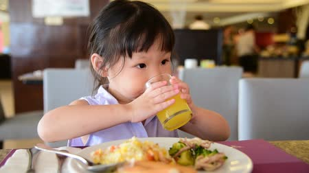 Little asian girl having breakfast on the table Wideo
