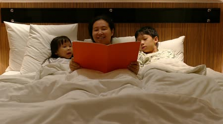 Asian mother read a book to her two children at bedtime Wideo