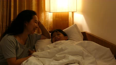Asian mother talking with her son at bedtime