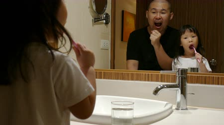 Asian father teaching his daughter to brushing her teach Wideo