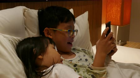 Asian children playing game in smart phone in bedroom
