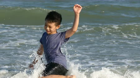Happy asian boy in the surf on a summer beach
