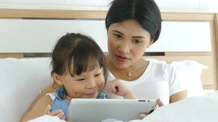 Young asian mother using tablet computer with her daughter on bed.