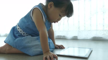 Little Asian girl watching cartoon on tablet computer at home