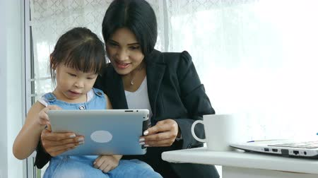Asian businesswoman with her daughter in office.