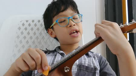 Young Asian boy playing ukulele on a chair at his home happily Wideo