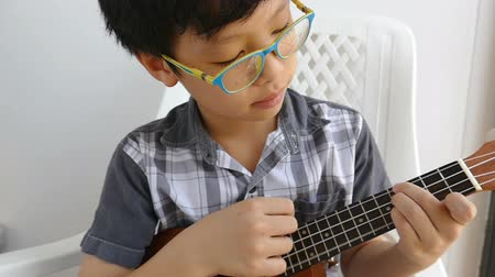 Young Asian boy playing ukulele on a chair at his home happily, slow motion. Wideo