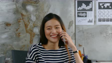 Beautiful Asian woman talking with friend by cellphone happily at office Wideo