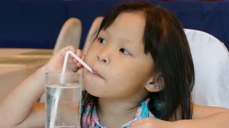 pretty little asian girl drinking water from glass with straw Wideo