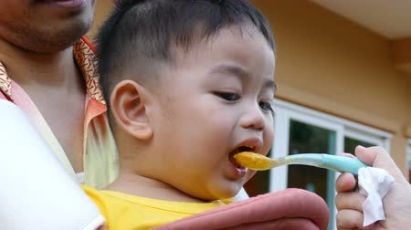 Little asian boy eating baby food ,mother feeding first solid food to her son. Wideo