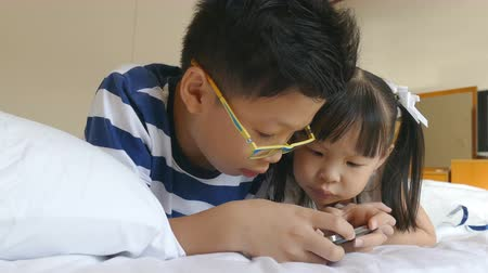 Asian children playing games on mobile phone in bedroom at home Wideo
