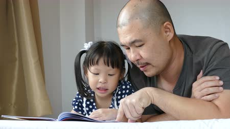Asian father teaching his daughter to reading book in bedroom at home Wideo