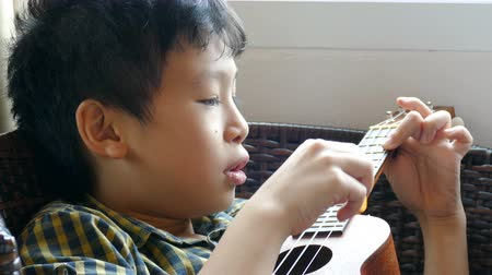 Little Asian child playing ukulele at home Wideo