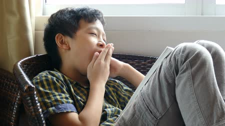 Young asian boy yawning between reading a book before examination