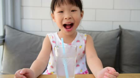 Pretty little asian girl drinking water from glass with straw