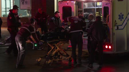 ölen : 4K UHD - Victim pulled in ambulance by restless paramedics. A team of restless paramedics are taking a victim of a shooting into an ambulance while performing CPR whit the help of police officers.