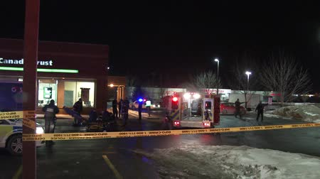 karetka : 4K UHD - Shooting victim being attended in bank parking lot. A would be thief with a gunshot wound is being worked on by paramedics and emergency crews in front of a bank with ATM and armored vehicle. Wideo