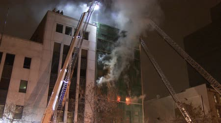 raport : 4K 60fps - Steady shot of fire & ladders. Tripod mounted shot of building on fire with firemen on the roof with flames and multiple ladders and fire trucks.