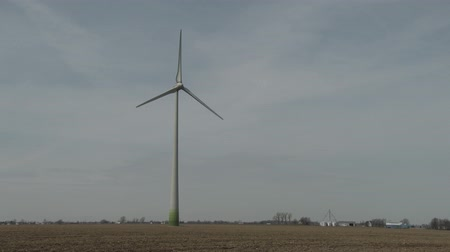 turbine : 4K UHD 60fps - Wind mill in motion full screen top to bottom. Single wind turbine turning slowly and producing clean energy with little town with church and farm in the background.