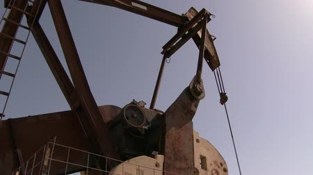 broca : Pumpjack counterweight and horsehead in closeup. 4K Close camera angle of old rusted out vintage pumpjack with heavy counterweight turning.  Shot in 4K UHD 3840 x 2160 at 60fps by The 4K Guy