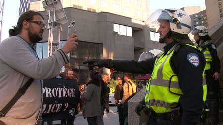 special unit : 4K UHD Protester filming riot officer too close. Man films a police officer with helmet and vest with his cellphone and riot officer makes him step back.