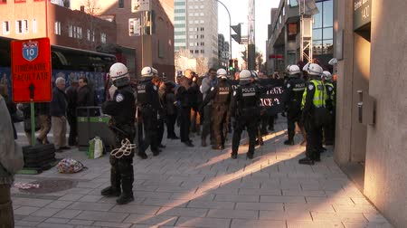 special unit : Riot police officers push back protesters. A group of tactical armed riot officers arrive on scene of protest and push back men holding anarchy sign.