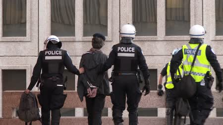 special unit : Protesters arrested by riot police. Two protesters are handcuffed with plastic restrain devices and carried away by police officer in riot uniform.